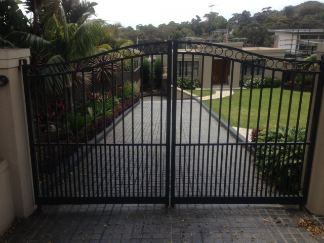 Automatic swinging gates Creators Range arch top with cirlces and mid height doggy bars Sydney