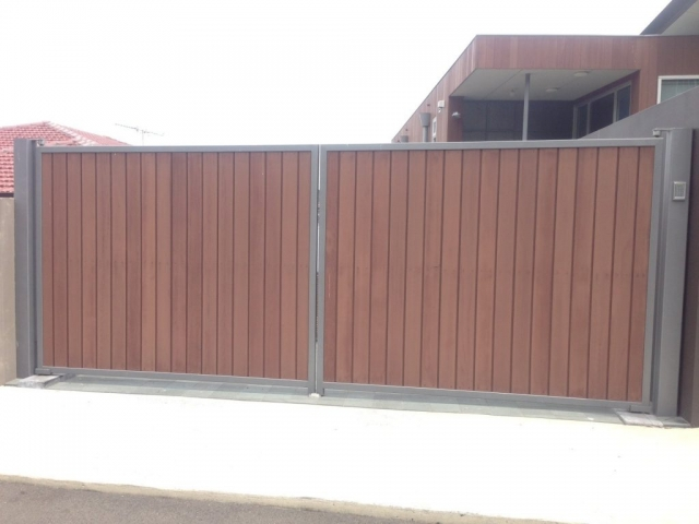 Automatic swinging driveway gates timber in steel frame Sydney